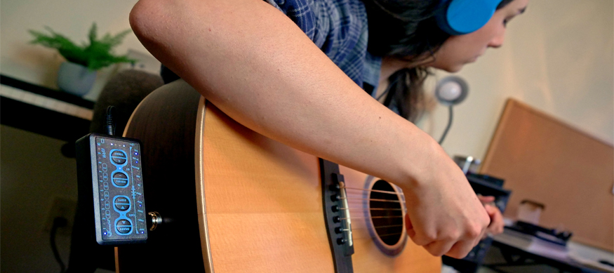 Young woman playing acoustic guitar with headphones on that connect to the Passport. The Passport is a small headphone guitar amp, black with blue accents, that plugs directly into the quarter-inch input of the guitar.